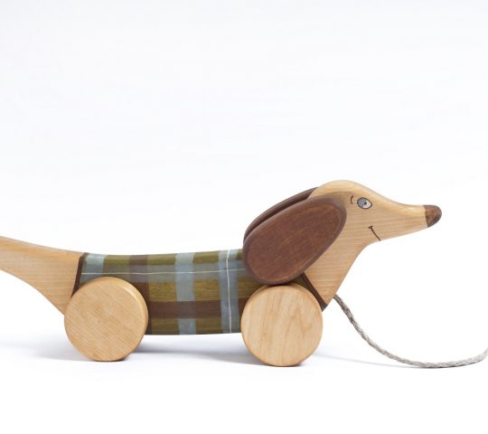 When organic wooden toy pull along dog is being pulled, he starts flapping his ears and swinging up and down with his front wheels.