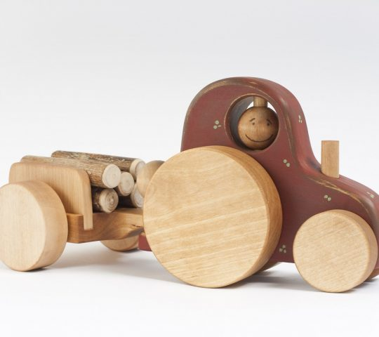 This handmade wooden tractor is really happy because he has a driver and a trailer. The driver can turn his head, uncouple the trailer and ride with the wind.